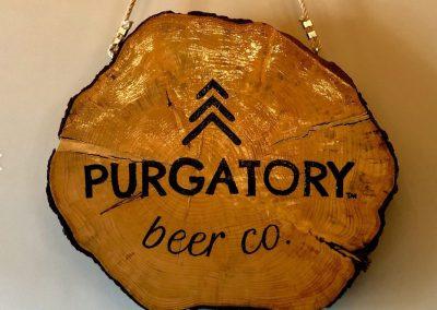 Purgatory Beer Logo on a log